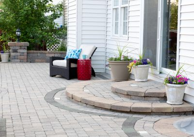 Stone Patio of Luxury Home with Steps to Back Door